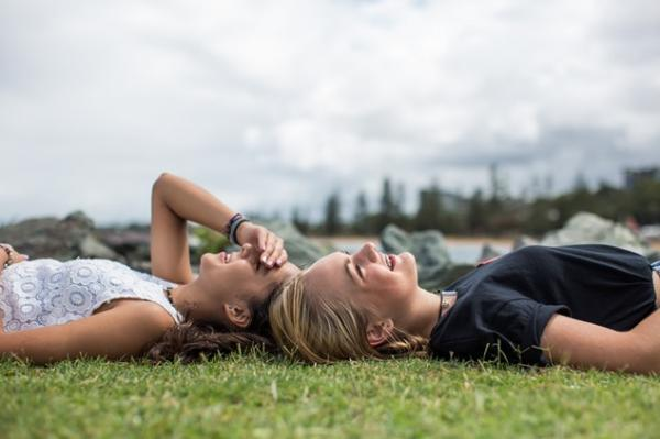 Two young people laying down on grass at a festival