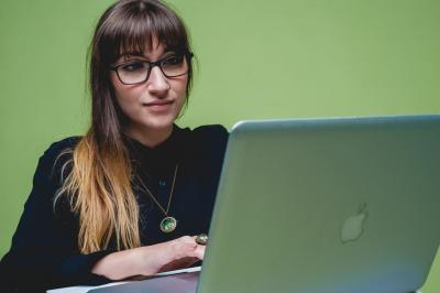 Young person with glasses uses a Macbook against a green background
