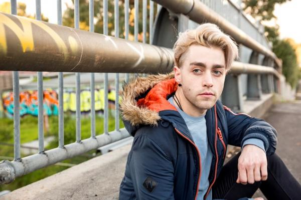 Young person stares past camera whilst sat against roadside railings.