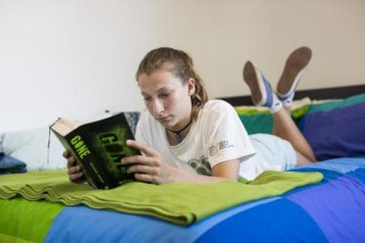 Person reading a book in bed